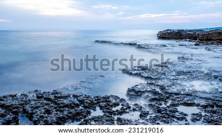 Rocky seashore and calm blue ocean under a cloudy sky with a shelf of rock jutting out into the sea. - stock photo