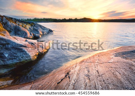 Rocky shore in the water at sunset