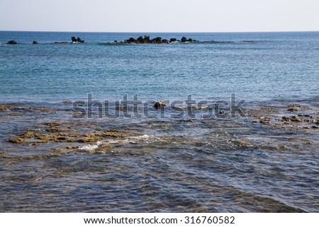 Rocky shore of the Mediterranean Sea. On the horizon, a natural stone breakwater. - stock photo