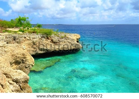 Rocky shore with stones and green trees. Turquoise calm wide tropical caribbean ocean on the left side. White clouds and blue sky, shining sun. Stones underwater close to the shore.