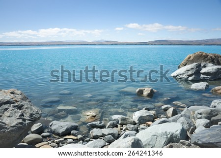Rocky shoreline of Lake Pukaki turquoise water and stoney beach. Snow feed lake in Canterbury, South Island NZ. - stock photo