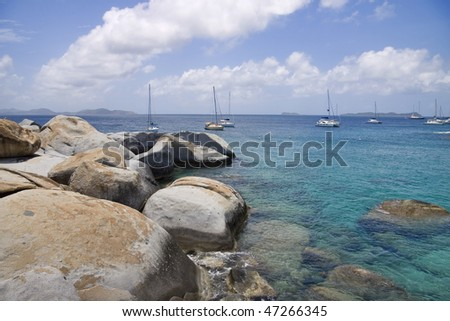 Rocky shoreline of the virgin islands and sailboats anchored in the water. - stock photo