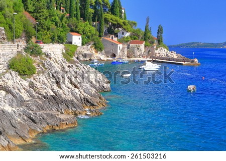 Rocky shores of the Adriatic sea and distant harbor with traditional buildings, Trsteno, Croatia - stock photo