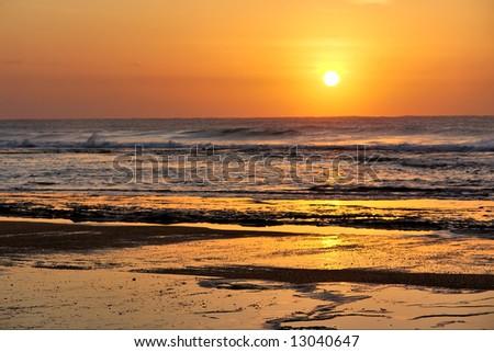 Rocky St. Lucia beach - sunrise. Shot in Sodwana Bay Nature Reserve, KwaZulu-Natal province, Southern Mozambique area, South Africa. - stock photo