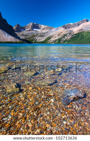 Rocky substrate visible under clear waters of Bow Lake in Banff National Park of Canada - stock photo