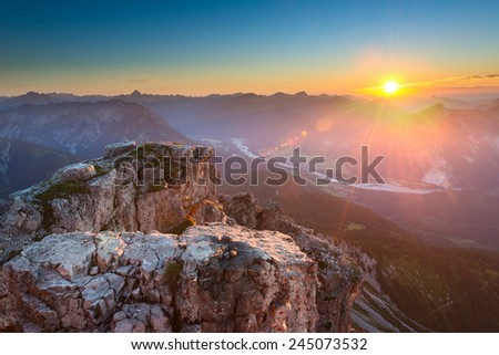 rocky top of mountain in tirol alps at colorful sunset - stock photo