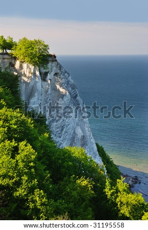 Rocky, tree-covered cliff looking out over the blue ocean. Ruegen Insel, Germany, Europe.