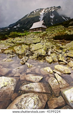 Rocky Water in the mountains with the old House - stock photo