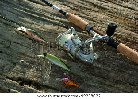 Rod, reel and wobblers on the wood