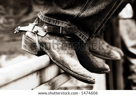 Rodeo cowboys' experienced boots & spurs on an iron rail #2 (shallow focus, high contrast black & white effect) - stock photo