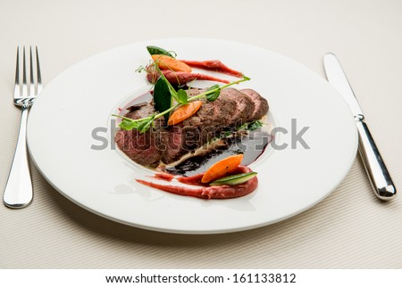 Roe deer fillet with vegetables, purple potato puree and red wine sauce - stock photo
