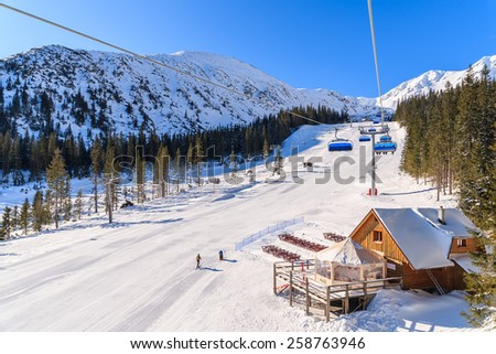 ROHACE VALLEY, TATRA MOUNTAINS - MAR 7, 2015: View of ski slope and restaurant in Rohace winter resort, Slovakia. Skiing is a popular sport in winter time. - stock photo