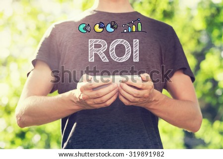 ROI concept with young man holding his smartphone outside in the park toward sunset - stock photo