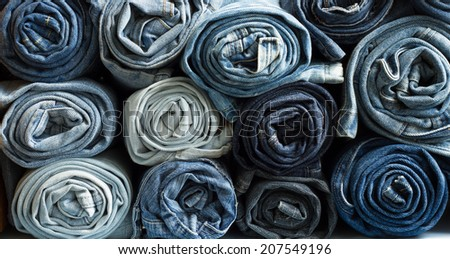 Roll blue denim jeans arranged in stack  - stock photo
