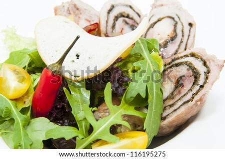 Roll meat with herbs and vegetables on a white plate