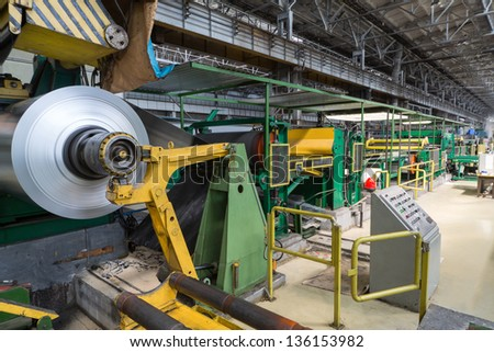 Roll of aluminum rotates on machine in workshop on rolling mill - stock photo