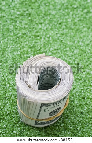 roll of cash on green textured background - stock photo