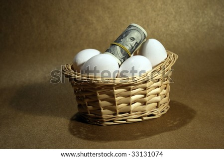 Roll of dollars in basket with eggs stock photo - stock photo