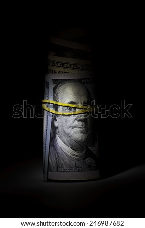 Roll of dollars in low-key. Benjamin Franklin blindfolded. The collapse of the world economy concept - stock photo