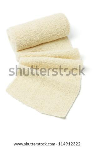 Roll of Elastic Crepe Bandage on White Background - stock photo