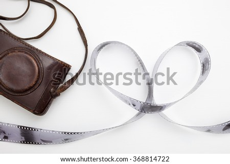 Roll of film, laid out in the shape of a heart and an old vintage camera. The love of antiques and hobby. - stock photo