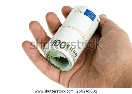 Roll of hundred euro in hand on white - stock photo