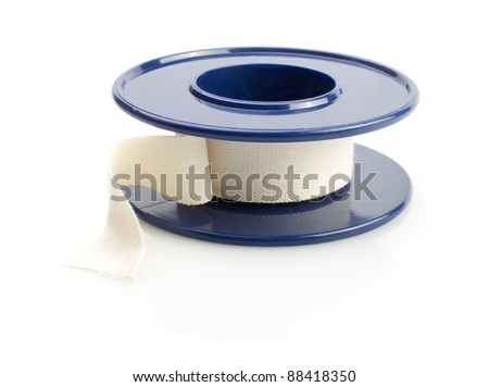 Roll of medical sticking plaster on white - stock photo