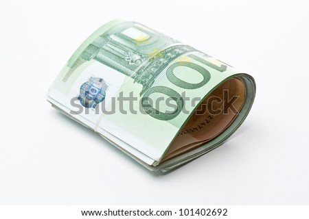 Roll of money and bow on white background - stock photo