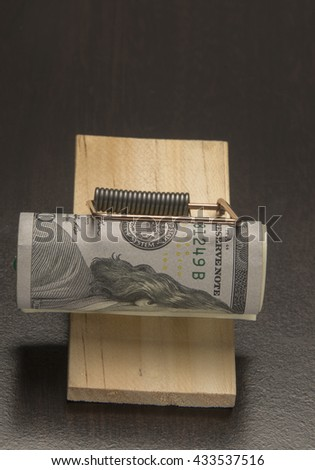 Roll of money is a spring trap/Money Trap/Currency is caught in a mouse trap - stock photo
