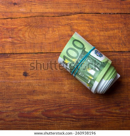 Roll of one hundred euro banknotes on wood background - stock photo
