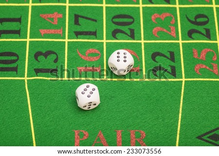 roll of the white dice on a game table in a casino - stock photo