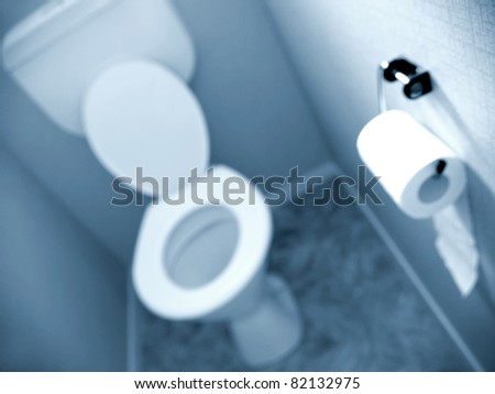 Roll of toilet tissue on wall of toilet - stock photo