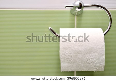 Roll of white toilet paper on metal paper holder  - stock photo