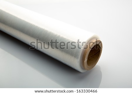 Roll of wrapping plastic stretch film on white background - stock photo