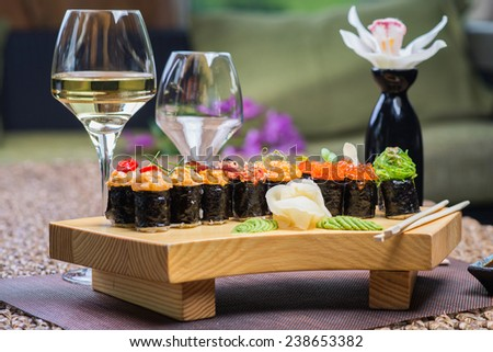 Roll set on wooden plate served at the restaurant, with wine and decor - stock photo