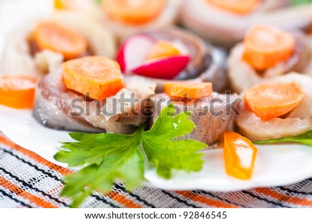 Roll with herring and parsley in bowl on holidays table - stock photo