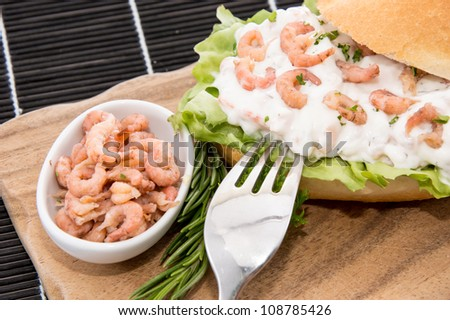 Roll with Shrimp-Salad on a cutting board at black background