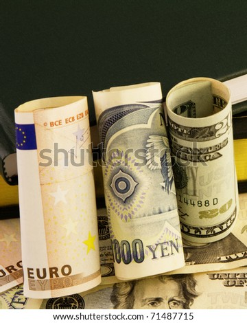Rolled  bills of euro, yen, and dollars is placed against ledgers and currency to depict global financial issues. - stock photo