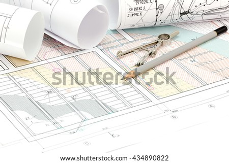 rolled blueprints and technical drawings with pencil and drawing compass - stock photo