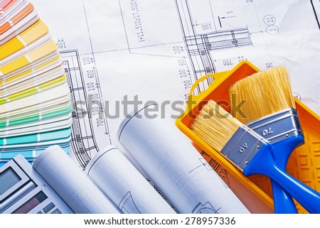 rolled blueprints calculator color palette paintbrushes tray  - stock photo