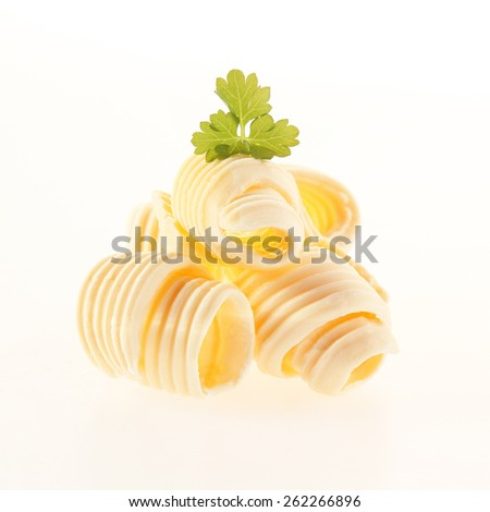 Rolled coils of fresh creamy butter garnished with parsley for a gourmet food presentation isolated on white - stock photo