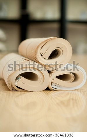 Rolled education book with reflection on the wood table - stock photo