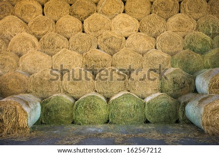 Rolled hay bales stacked in storage - stock photo