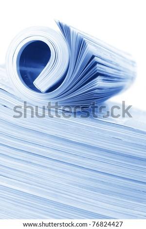 Rolled magazine on magazine stack. Toned monochrome image. - stock photo
