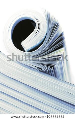 Rolled magazine on magazines stack. Toned image. - stock photo