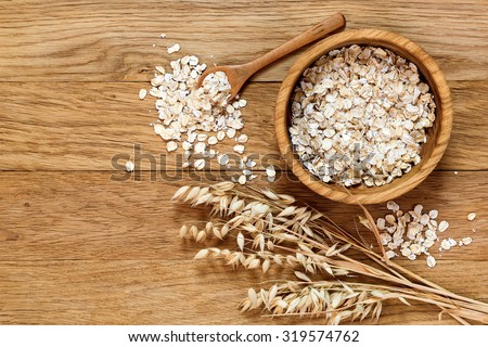 Rolled oats and oat ears of grain on a wooden table, copy space - stock photo
