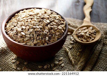 Rolled oats in brown bowl on linen with natural sunlight, close up - stock photo