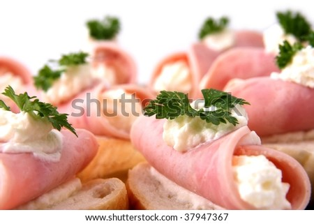 Rolled slices of ham filled with horseradish cream - stock photo