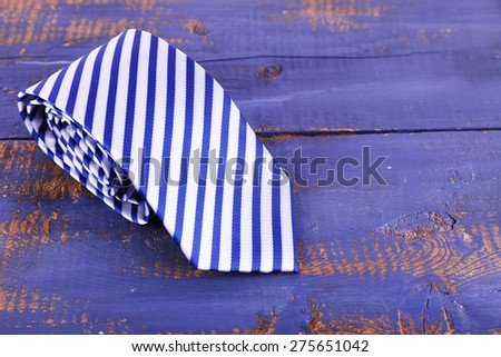 Rolled striped tie on wooden background - stock photo