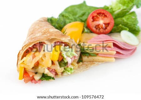 Rolled thin pancakes with ham, cheese and vegetables - stock photo